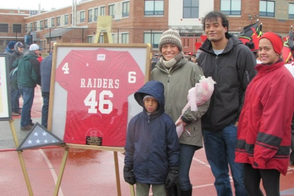Kevin Houston's wife, Meiling, and their three children stand proudly beside his retired #46 jersey that will be displayed prominently at Barnstable High School. Meiling was presented with a jersey and flowers at the ceremony in honor of her late husband's heroism.